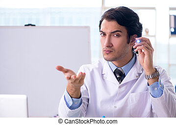 Young handsome doctor in front of whiteboard