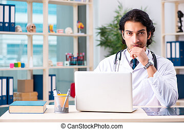 Young handsome doctor working in clinic