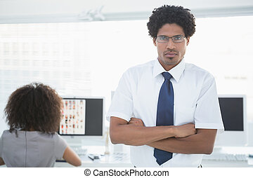 Young handsome editor frowning at camera with colleague working