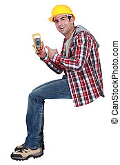 young handsome electrician pointing at tester