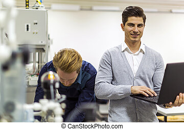 Young handsome engineer checking data on a laptop