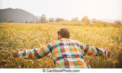Young handsome farmer standing in wheat field and looking forward at sunset