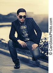 Young handsome fashion man in sunglasses at sunset