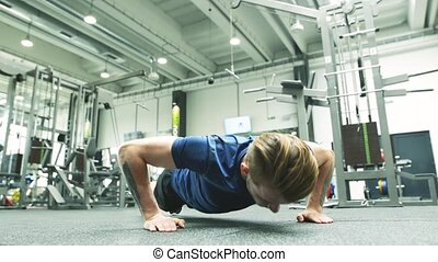 Young handsome fit man in gym doing push ups