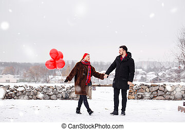 Young handsome guy and girl with a balloons walking