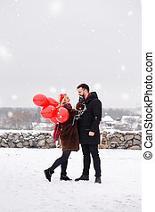 handsome guy and girl with a balloons walking