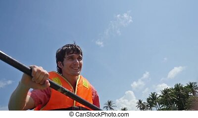 Young handsome Guy Paddling On Kayak Boat In Sea in slow...