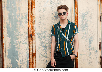 young handsome guy with sunglasses in stylish beach clothes with a bag on the street near the metal wall