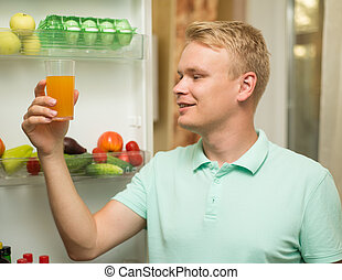 Young handsome happy man smiling, holding a glass of juice is in the fridge
