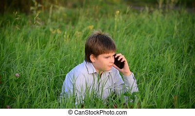 Young handsome happy modern teen talking on phone in summer...