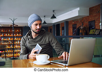 Young handsome hipster man with beard is using computer in cafeteria