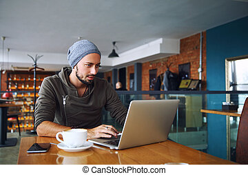 Young handsome hipster man with beard is using laptop in cafeteria