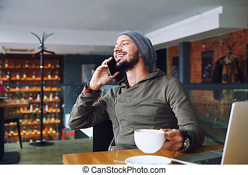 Young handsome hipster man with beard sitting in cafe talking mobile phone, holding cup of coffee and smiling. Laptop on wooden table.