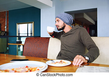Young handsome hipster man with beard sitting in cafe talking mobile phone, holding cup of coffee. Laptop on wooden table.