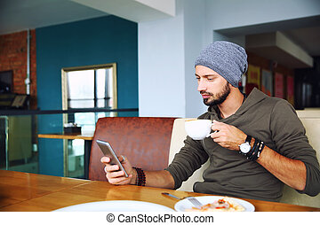 Young handsome hipster man with beard sitting in cafe using a mobile phone, holding cup of coffee.