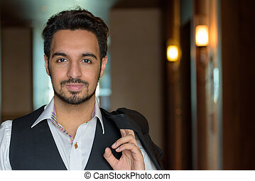 Young handsome Indian man holding jacket in the corridors of hot
