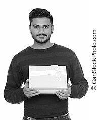 Young handsome Indian man ready for Valentine's day holding gift box