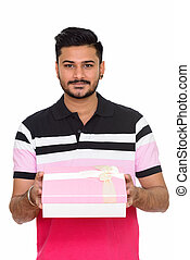 Young handsome Indian man ready for Valentine's day holding gift