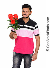 Young handsome Indian man ready for Valentine's day holding rose