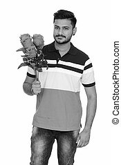 Young handsome Indian man ready for Valentine's day holding roses