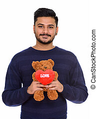 Young handsome Indian man ready for Valentine's day holding tedd