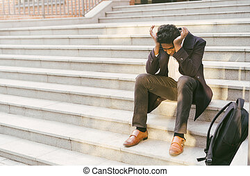 Young handsome Indian man in a white shirt and a business jacket. Sitting sad on the steps of the building with his hands clasped. The concept of dismissal, layoffs, unemployment. University Exam