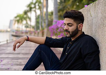 Young handsome Indian man thinking while looking down