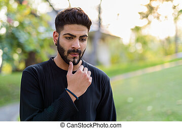 Young handsome Indian man thinking