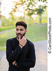 Young handsome Indian man thinking with hand on lip on the side