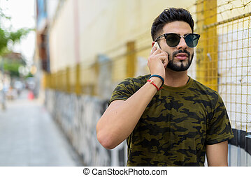 Young handsome Indian man wearing sunglasses while thinking