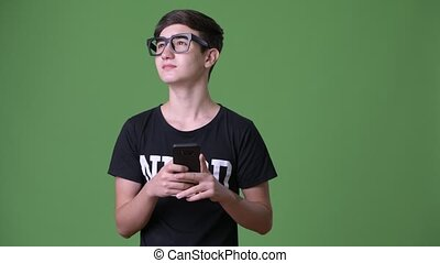 Young handsome Iranian teenage boy against green background