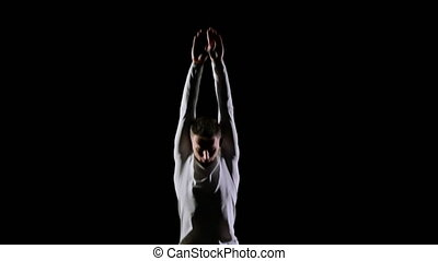 Young handsome male acrobat gymnast in white clothes on a...