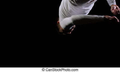 Young handsome male acrobat gymnast in white clothes on a black background makes jumps and shows tricks with rotation and somersault on a trampoline in slow motion