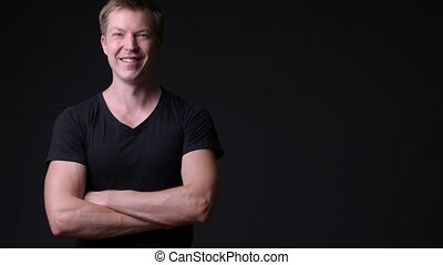 Young handsome man against black background