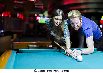 Young handsome man and woman flirting while playing snooker