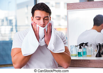 Young handsome man applying face cream