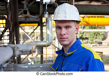 Young handsome man constructor in white hardhat and blue...