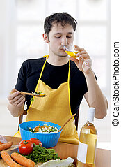 Young handsome man cooking salad on kitchen