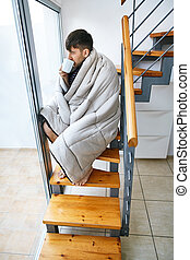 Young handsome man covered with blanket drinking hot coffee sitting on stairs