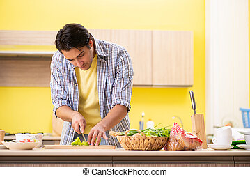 Young handsome man cutting pepper in the kitchen
