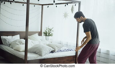 Young handsome man dancing and playing like guitarist near bed at home