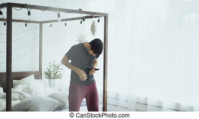 Young handsome man dancing and singing like rock musician near bed at home