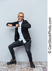 Young handsome man dancing over gray background