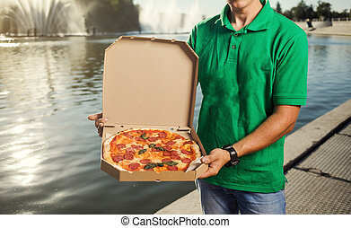 Young handsome man delivering pizza to a customer