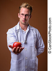 Young handsome man doctor against brown background