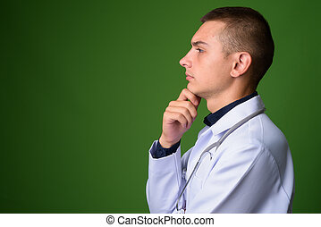 Young handsome man doctor against green background