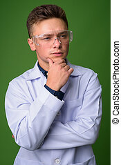 Young handsome man doctor wearing protective glasses against gre