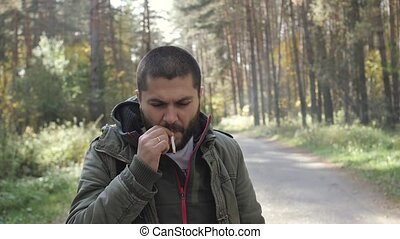 Young handsome man dressed in a jacket in a autumn forest confidently smokes a cigarette, let the smoke.