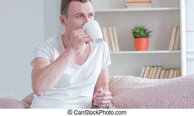 Young handsome man drinking tea at home.