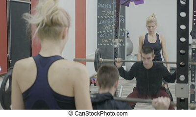 Young handsome man exercising in the gym with heavy dumbbells to work out his arms while his female instructor helps him